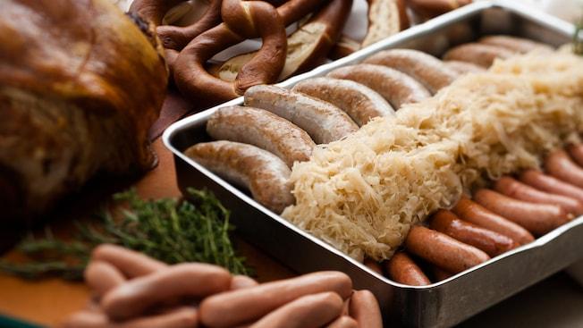 Assadeira com chucrute e 2 tipos de salsicha alemã sobre uma mesa, ao lado de carnes e pretzels