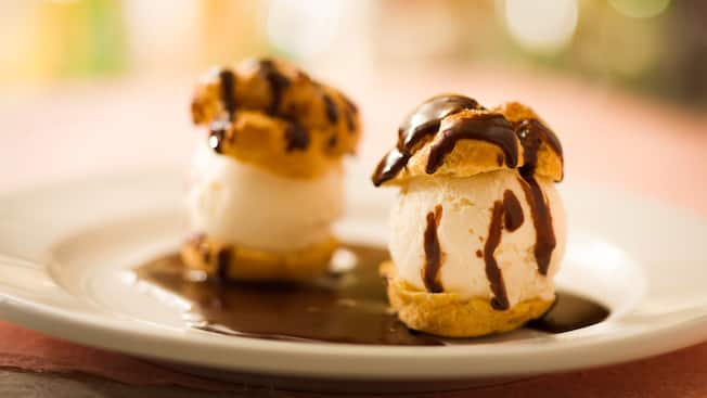 Two puff choux pastries filled with vanilla ice cream and sprinkled with chocolate sauce on a plate
