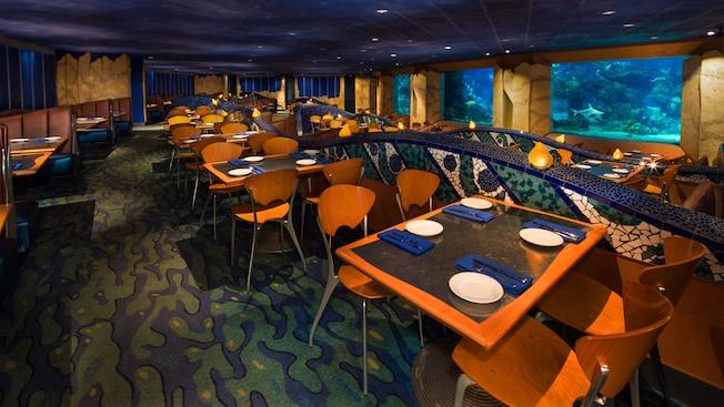 Vista alternativa de las mesas en el restaurante Coral Reef junto a las ventanas hacia el acuario
