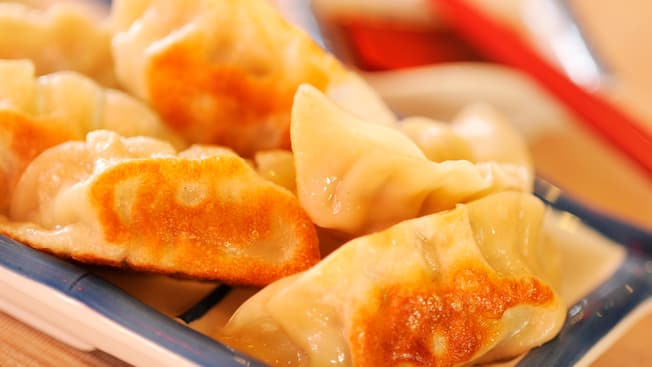 A selection of savory pot stickers which have been pan-fried to a crisp and served on a small plate