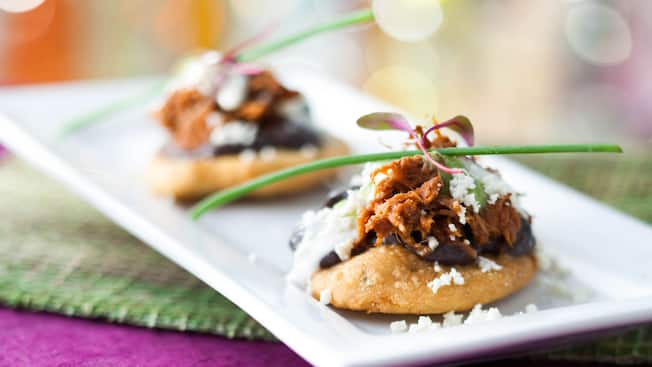 Corn cakes topped with black refried beans, pork, queso fresco, sour cream and tomatillo sauce