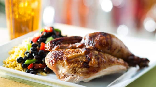 Roasted chicken on a plate with black beans and yellow rice