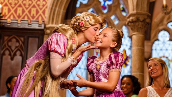 La princesse Raiponce embrasse une jeune fille sur la joue au Cinderella's Royal Table
