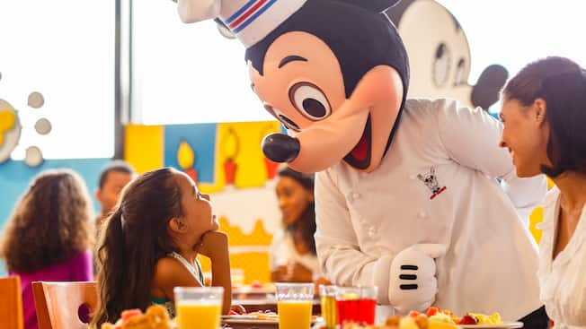 Chef Mickey greets a little girl and her mother at their breakfast table