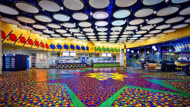 Vibrantly speckled floor and trim in primary colors with bright white overhead lights