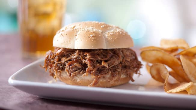 A barbecue pork sandwich served with potato chips