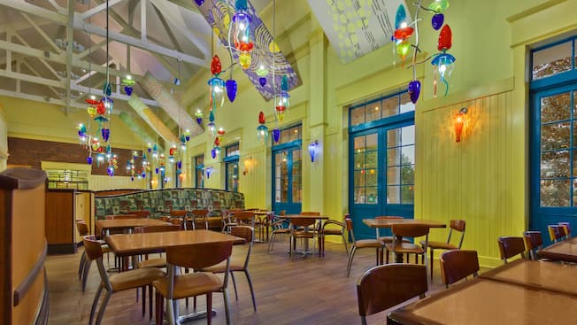 Área de comidas aireada y colorida con móviles coloridos que cuelgan de un techo alto en el restaurante The Artist's Palette