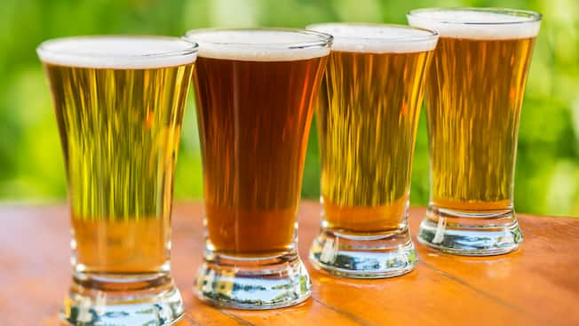Four glasses of beer on a wood tabletop
