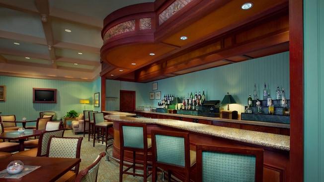 Tres sillas de bar frente a una barra de granito, con estantes de botellas de licor contra la pared