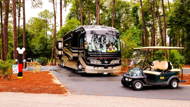 Golf cart parked in front of a gleaming motor coach parked at a wooded RV campsite