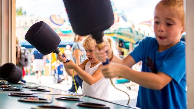 Un niño y una niña posan con mazos en las manos en el juego para golpear dinosaurios