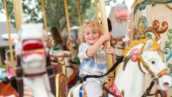 Un niño monta el Marketplace Carousel en Disney Springs.
