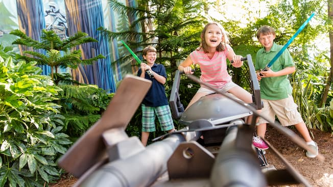 Kids with lightsabers on a Star Wars-themed prop at Star Tours: The Adventures Continue