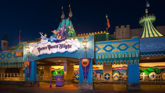 Vista noturna da Peter Pan's Flight com estátuas do Peter Pan, Wendy e seus irmãos acima da placa