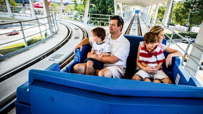 Una madre y un padre, cada uno sosteniendo a un hijo pequeño, pasean en Tomorrowland Transit Authority PeopleMover