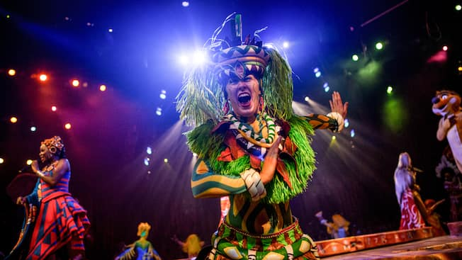 Costumed performers from Festival of the Lion King wave from the stage