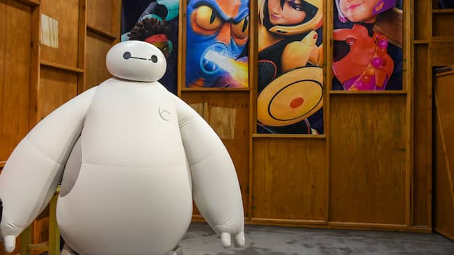 Baymax stands in front of portraits of his teammates from Big Hero 6