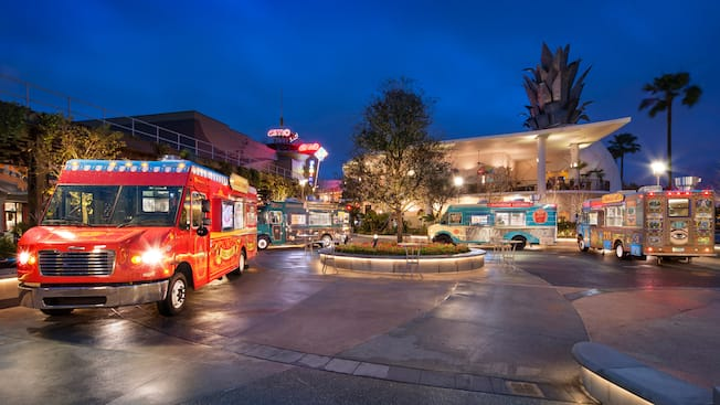 Food trucks parked beneath the vibrant evening lights of Disney Springs at Walt Disney World Resort