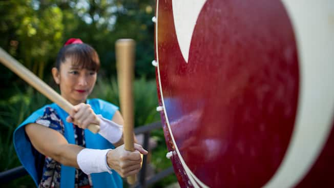 A female member of the percussive troupe Matsuriza pounds a Taiko drum at the Japan Pavilion