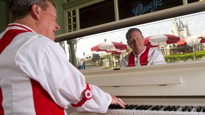 Un pianista toca el piano en Casey's Corner con el Cinderella Castle reflejado en un espejo