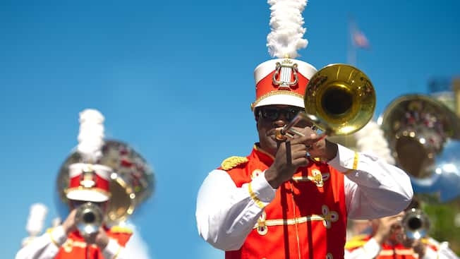 Trombone player marches in place with the Main Street Philharmonic brass band at Main Street, U.S.A.