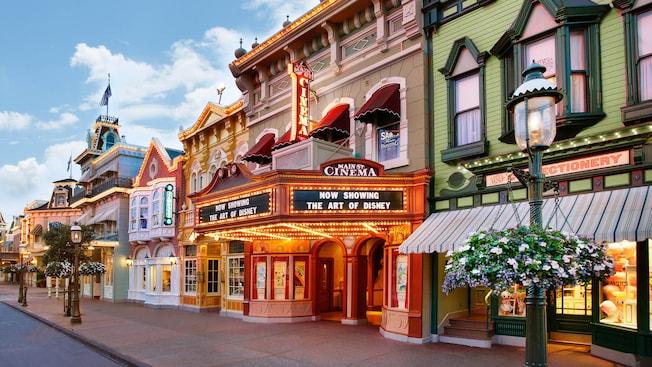 Vitrinas en una calle cerca de lámparas y de un teatro con un cartel que dice Main Street Cinema Now Showing the Art of Disney