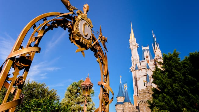An ornate iron entrance gate with Cinderella Castle in the background