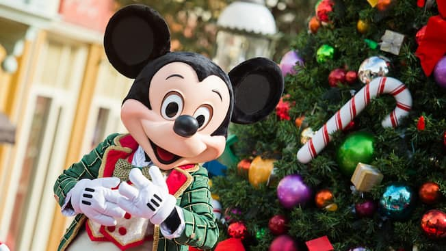 Mickey Mouse stands next to a Christmas tree