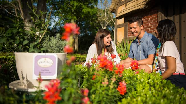 Two female Guests and their male companion enjoy an Epcot International Flower & Garden Festival tour