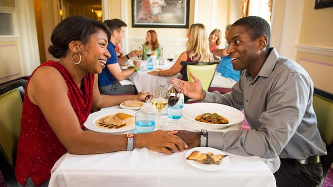 Amidst other Monsieur Paul diners, a smiling couple holds hands and chats at a table filled with delicious-looking entrees, crusty bread and glasses of red and white wine