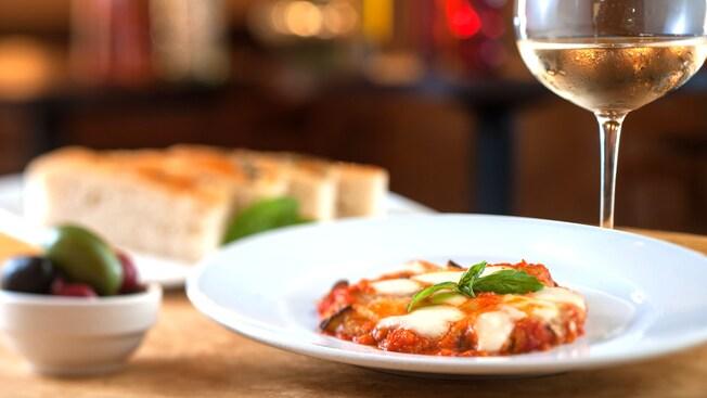Cocina Gourmet italiana preparada con salsa marinara y mozzarella, y servida junto a una copa de vino