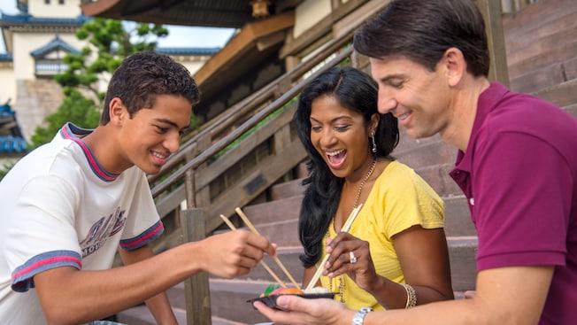 En una escalera con peldaños de piedra, con una ambientación al estilo japonés, una mujer y un hombre acercan sus palillos al contenedor que incluye una variedad de sushi que otro hombre sostiene