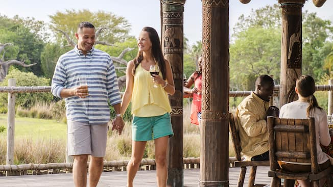 5 people drink wine near a gazebo and a forest