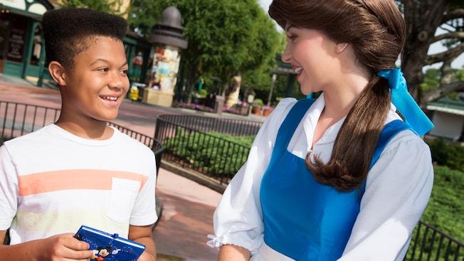 Um Visitante sorri ao encontrar a Belle durante um Encontro com Personagem no Epcot