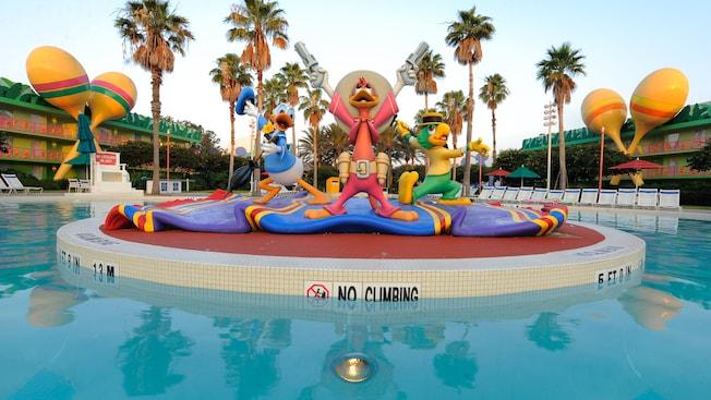 Estatuas de Los tres caballeros, el Pato Donald, José Carioca y Panchito, en el centro de la piscina con forma guitarra Calypso Pool