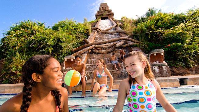 6 jóvenes adolescentes disfrutan en la piscina The Lost City of Cibola, una excavación de temática arqueológica con un tobogán de piscina