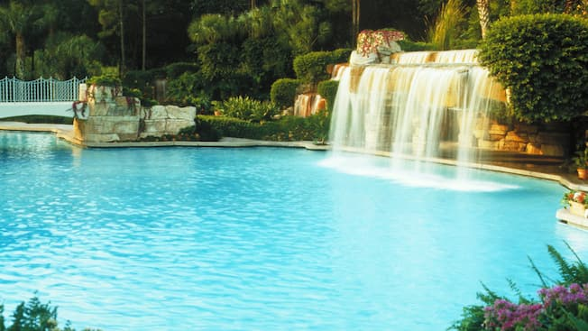 Light-blue pool with a waterfall framed by lush foliage at the Walt Disney World Dolphin Hotel