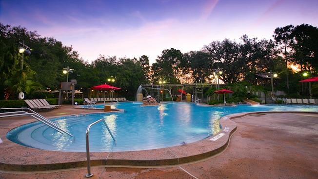 La piscina Ol' Man Island swimmin' hole al atardecer, rodeada de reposeras y sombrillas de color rojo