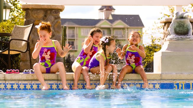 4 little girls in Ariel swimsuits laughing hysterically as they sit and splash at the edge of a pool