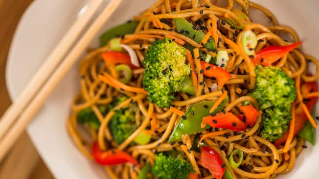 A bowl containing noodle salad with bell peppers, sesame seeds, broccoli, bean pods, shredded carrots and green onions
