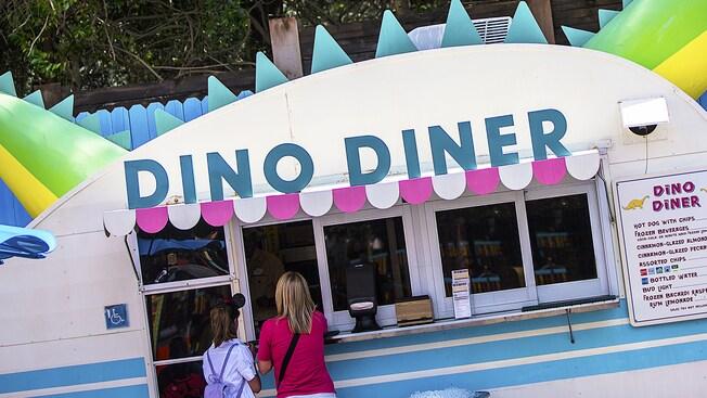 Les visiteurs font la queue pour prendre une commande à la remorque Dino-Diner, décorée sur le thème des dinosaures