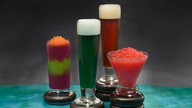 Two frozen beverages topped with boba balls, and two beers served in pilsner glasses