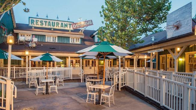 Área de refeições externa no Restaurantosaurus com inovadora decoração no pátio, guarda-sol, cadeiras e mesas