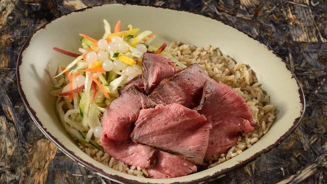 Uma tigela de carne bovina fatiada e grelhada em fogo baixo, servida com salada de legumes, bolas de tapioca e arroz integral