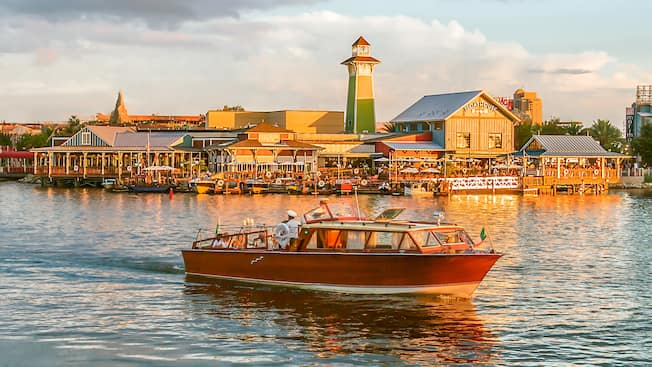 A small ship sails along the water in front of The BOATHOUSE at Disney Springs
