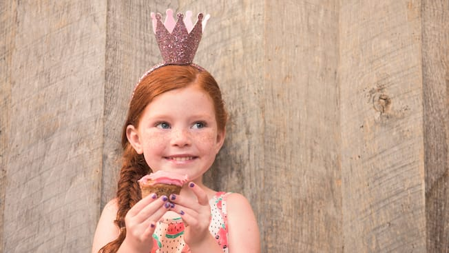 A little girl wears a crown and holds a cupcake