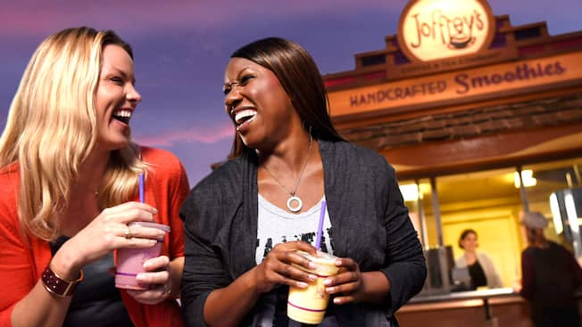 2 women share a laugh together while enjoying smoothies outside a handcrafted smoothie venue