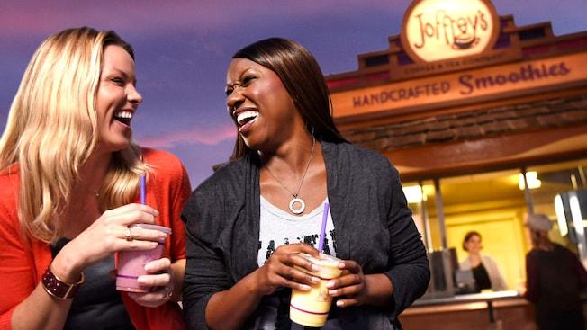2mujeres se ríen juntas mientras disfrutan de batidos fuera de un puesto de batidos artesanales