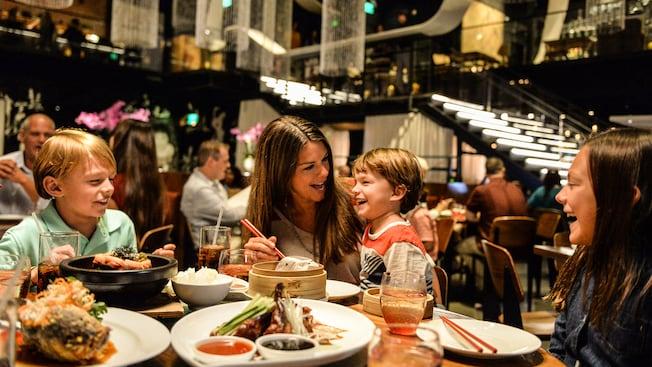 Una madre y sus 3 niños sonríen mientras comen en un comedor moderno en Morimoto Asia