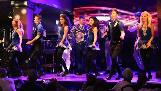 Bailarines irlandeses actúan en un escenario con una banda en vivo